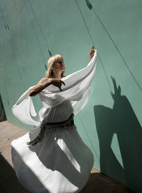 stock photo of ecstacy  - Woman in white dress moving and dancing in the strong sun - JPG