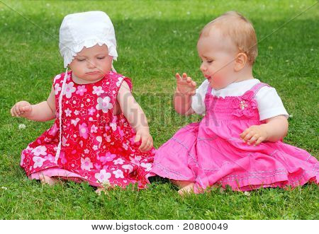 Two little sisters sitting on a grass.