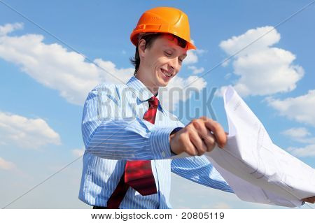 young engineer in a blue shirt and yellow helmet
