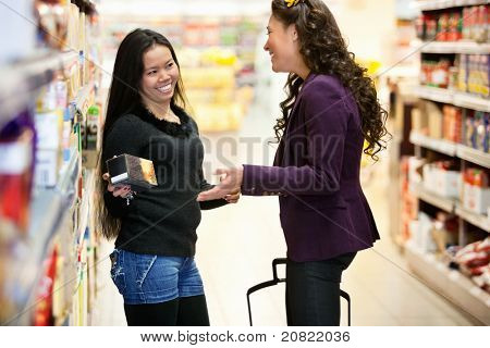 Cheerful women having conversation in shopping centre while holding product