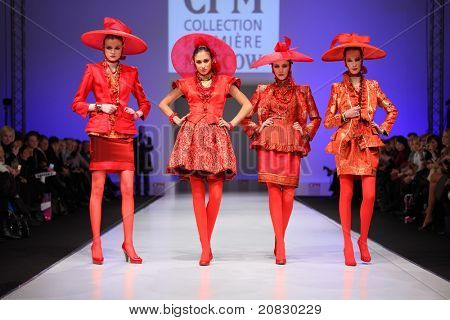MOSCOW - FEBRUARY 22: Four women wear red suits from Slava Zaytzev walk the catwalk in the Collection Premiere Moscow, a fashion industry platform of IGEDO Company, on February 22, 2011 in Moscow, Russia.