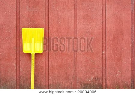 Yellow Toy Shovel Against Red Barn Wall