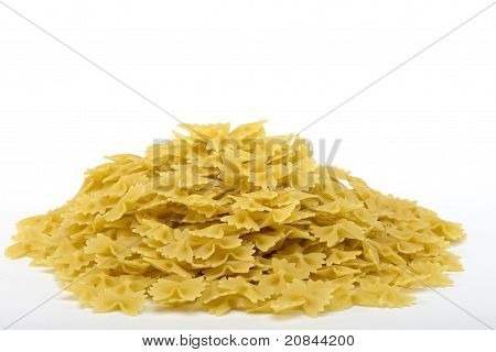 Raw bow tie pasta noodles in a pile