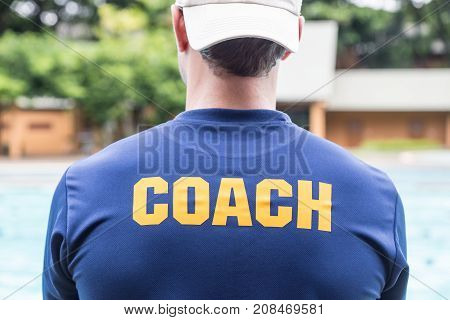 poster of back of a sport coach's blue shirt with the yellow Coach word written on it; good background for sport or coaching theme