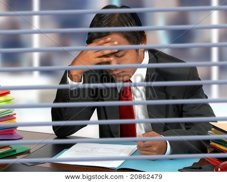 Businessman Reading Documents At His Desk