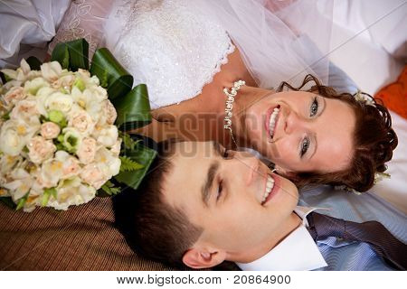 Newlywed Couple Lying Together On The Bed