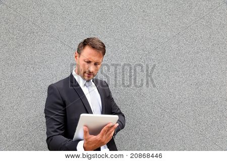 Businessman using electronic tablet leant against wall