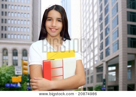 Brunette student young girl teen latin holding books modern city buildings