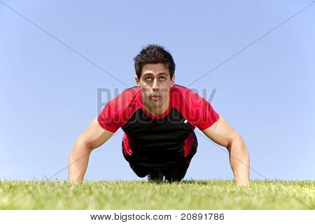 Athlete man at the park making some push up