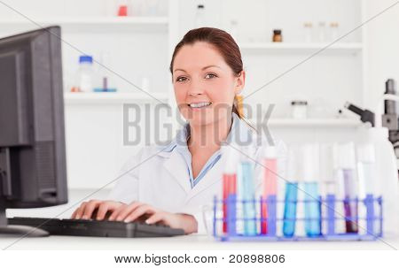 Red-haired Scientist Typing A Report With Her Computer Looking At The Camera