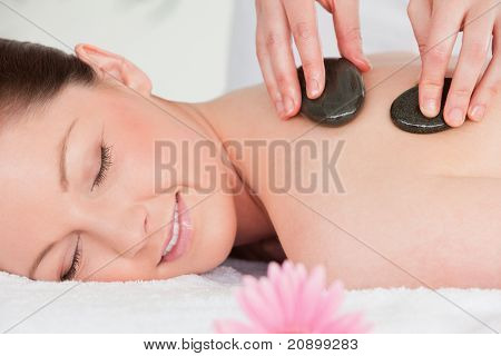 Young Woman Closing Her Eyes While Having A Hot Stone Massage