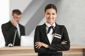 Female hotel receptionist at workplace poster