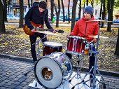 Festival music band. Cropped shot of male musicians playing on percussion instruments in city park.  poster