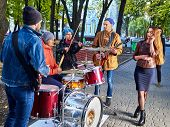 Festival music band. Friends playing on percussion instruments in city park. Fountain and trees in t poster