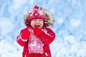 Baby Playing With Snow In Winter. poster