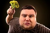 Diet fat man eating healthy food . Health breakfast with vegetables broccoli for overweight person.  poster