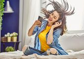 Cheerful young woman listening music in headphones sitting on the bed in the room at home. poster
