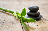Close up of stacked hot stones with green bamboo on wooden table. Black massage stones necessary for poster