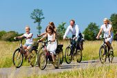 stock photo of dirt-bike  - Family with baby and three girls having a weekend excursion on their bikes on a summer day in beautiful landscape - JPG