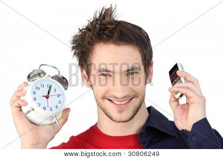 Man holding alarm clock and mobile telephone