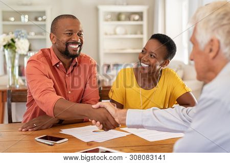 poster of Mature black husband shaking hands with senior agent on taking loan. Happy african couple sealing wi