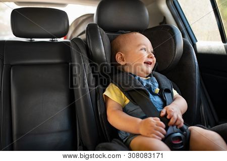 poster of Portrait of cute smiling toddler sitting in car seat and looking outside the window. Little boy sitt