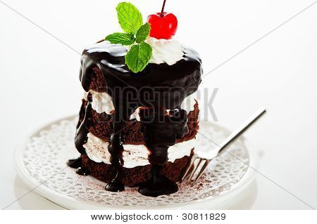 A Small Chocolate Cake With 2 Layer White Cream, Cherry And Mint  On Top On A White Background As A