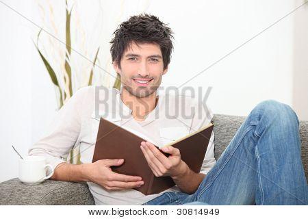 a man reading a book on couch