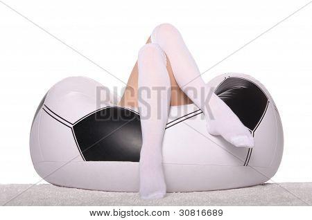 Torcedor de futebol e futebol em uma cadeira inflável