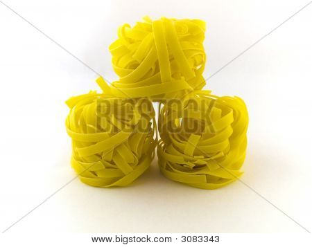 Three Rolls Of Pasta Tagliatelli On White Background