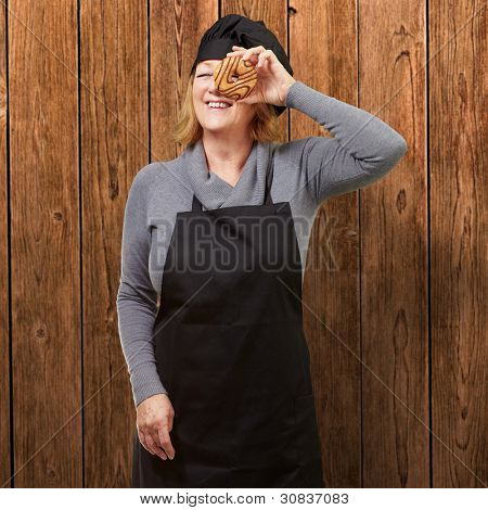 Middle aged cook woman looking through a donut against a wooden wall