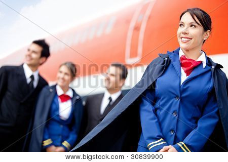 Flight attendant with cabin crew and an airplane at the background