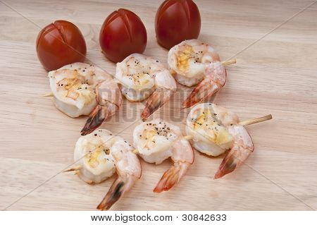 delicious fresh shrimp on a wooden board peeled with Skewer and tomatoes