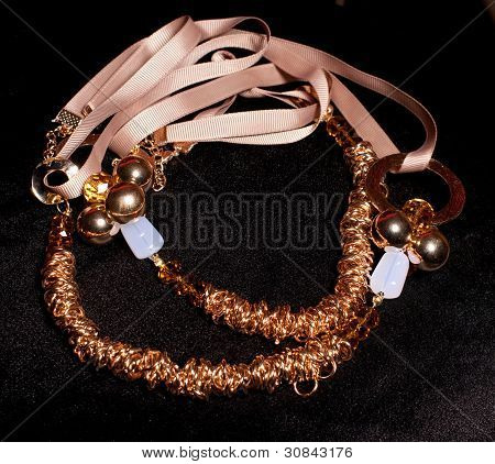 Gold jewelry c ribbons and stones on a black background