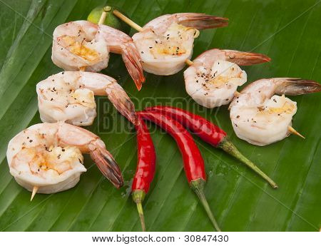 delicious fresh shrimp on a green banana leaf peeled with Skewer and chili