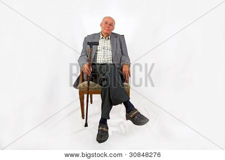 old man sitting in the armchair and looks very confident and happy