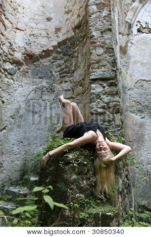 Blonde girl laying on a stone