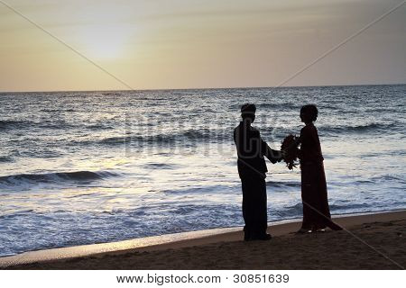 Married Couple Stands Happy  At The Beach In Sunset