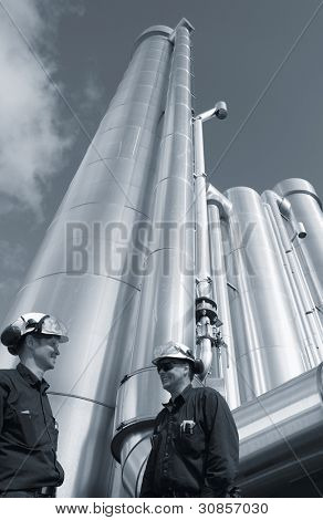 two oil workers with giant gas and oil pipelines in background, duplex blue toning concept