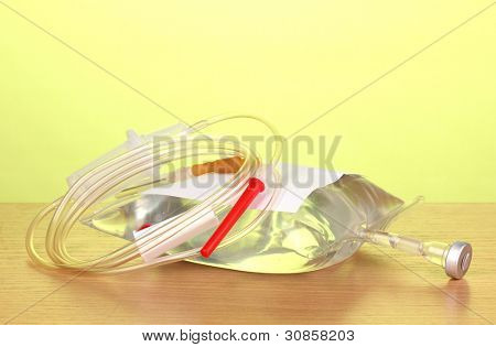 Bag of intravenous antibiotics and plastic infusion set on wooden table on green background