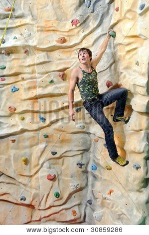 active young man on rock wall in sport center