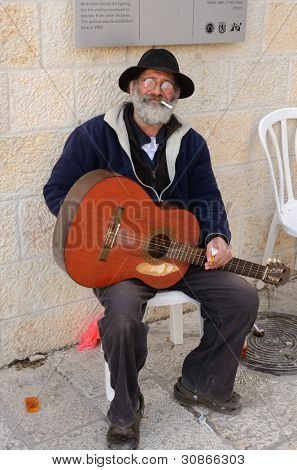 JERUSALEM - FEBRUARY 23: A classical guitarist takes a break from busking February 23, 2012 in Jerusalem, IL. Busking dates from antiquity and is present in every culture in the world.