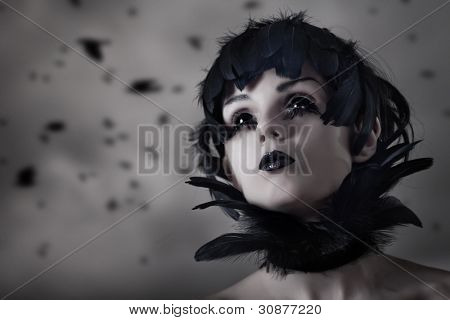 Crow girl with feather wig and black eyes, real contact lenses and makeup