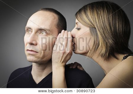 Young woman telling her husband a secret