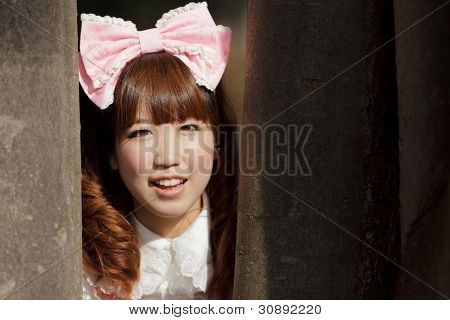 japanese woman in sweet lolita cosplay  hiding in forest