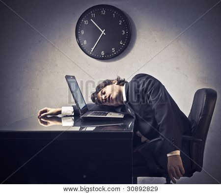 Tired businessman sleeping on a laptop with clock in the background
