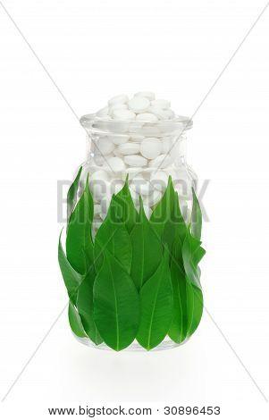Herbal supplement pills in medicine bottle with fresh leaves - alternative medicine concept