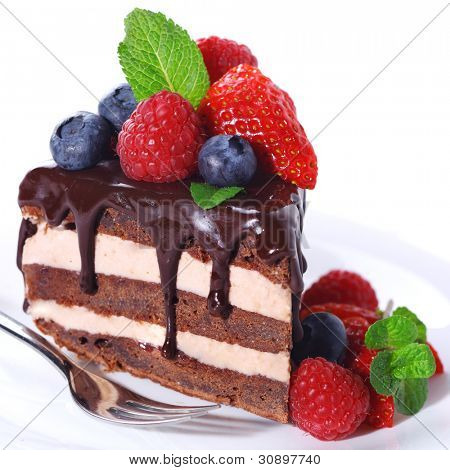 Piece of chocolate cake with icing and fresh berry on white isolated background