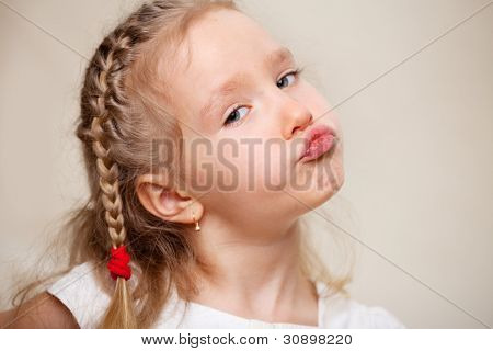Grimacing child. Capricious little girl.