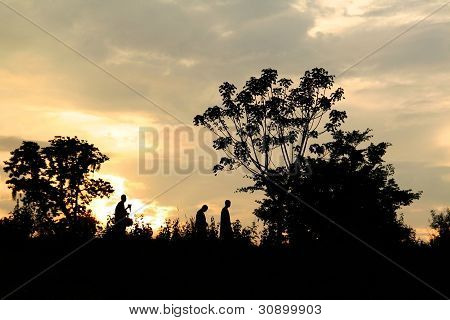 Three Men Walking in Sunset Sky